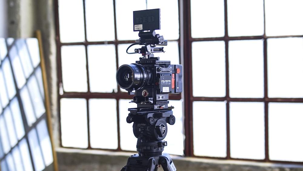 black filming camera on tripod near window