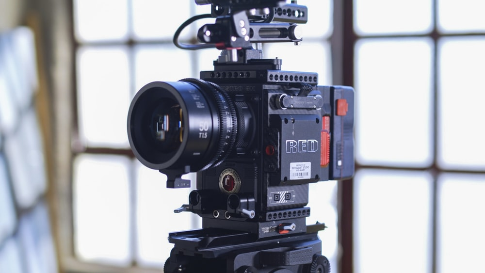close-up photo of black camera with tripod
