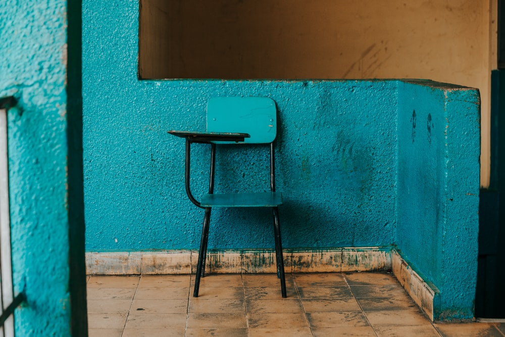 blue and black writing chair beside wall