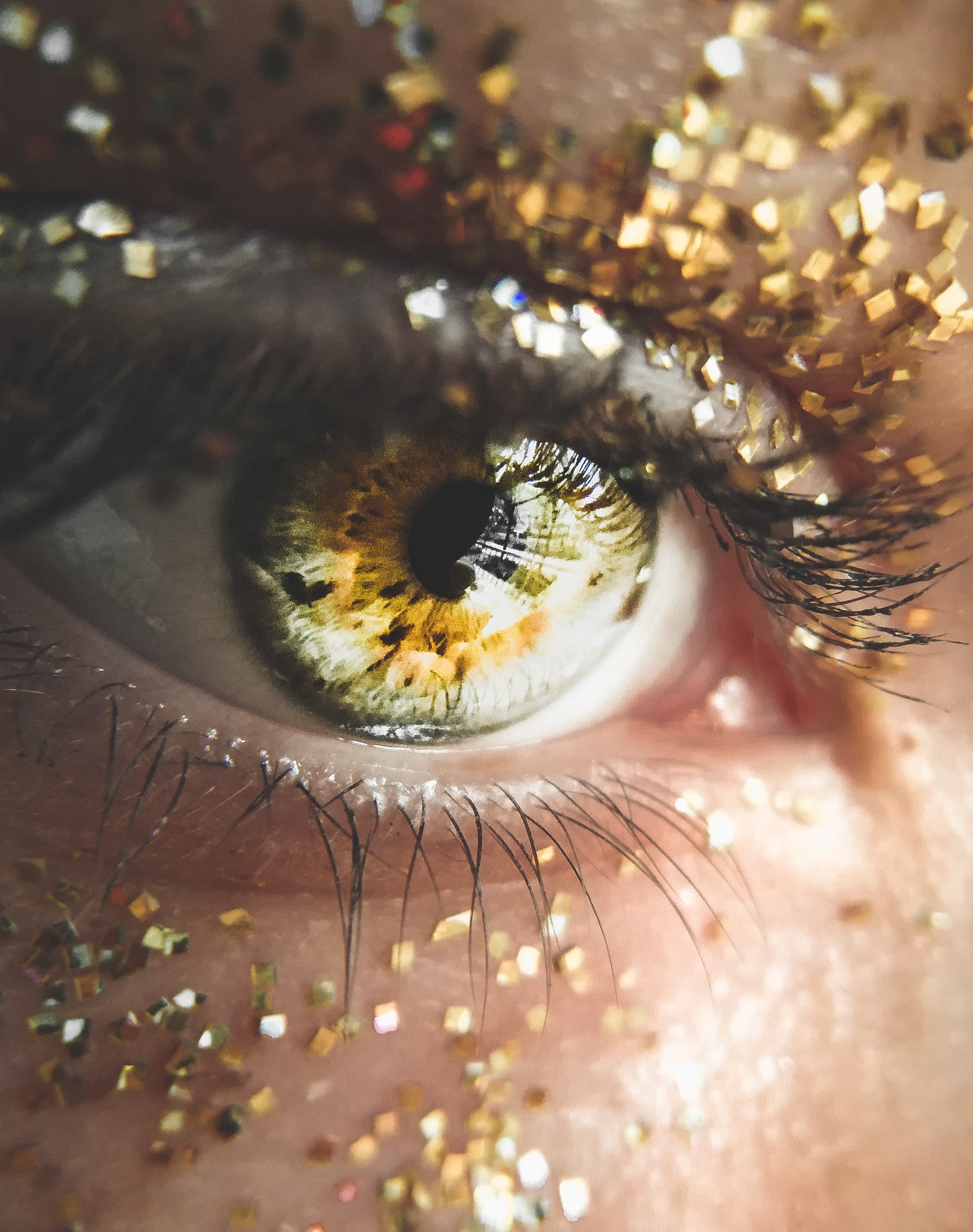 person showing yellow eye with glitters