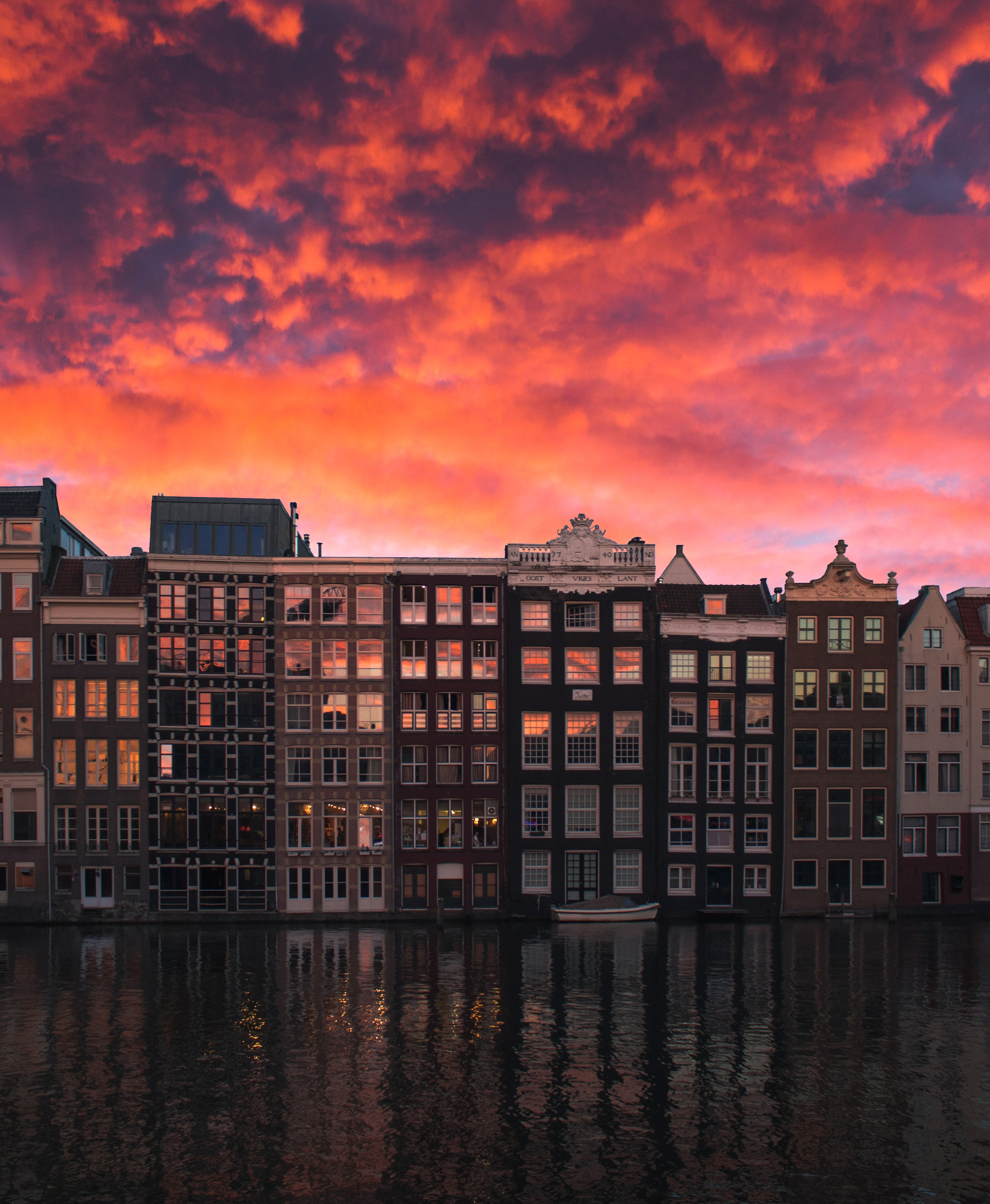 row of buildings near body of water during golden hour