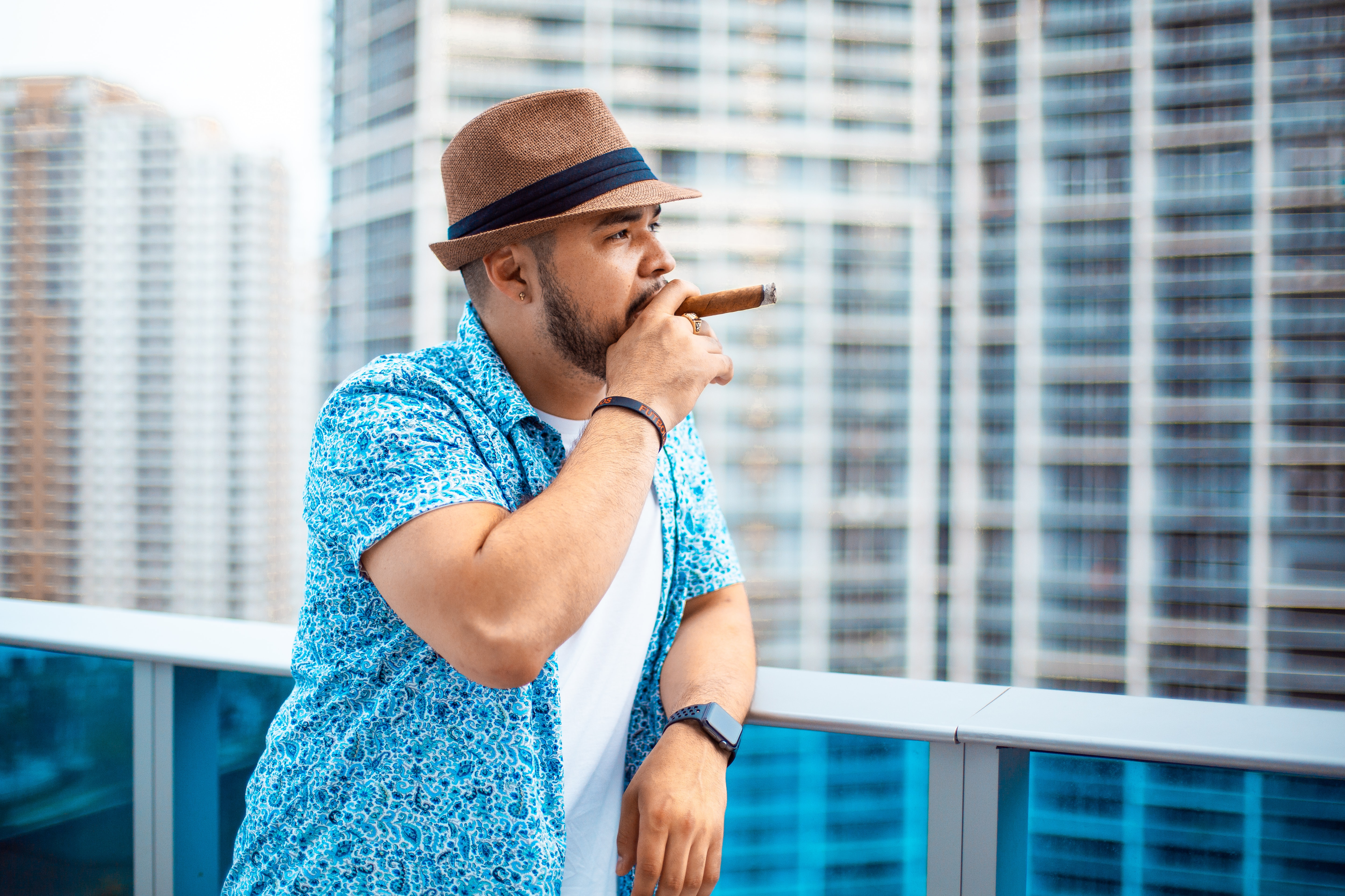 person leaning against white metal railing while smoking cigar