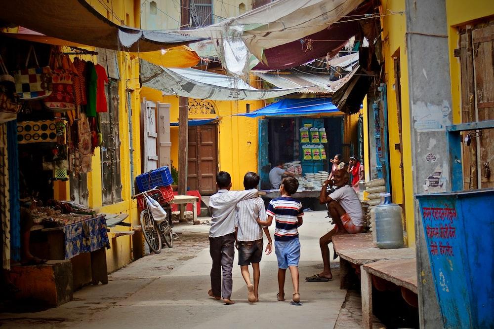 three boys walking between buildings at daytime