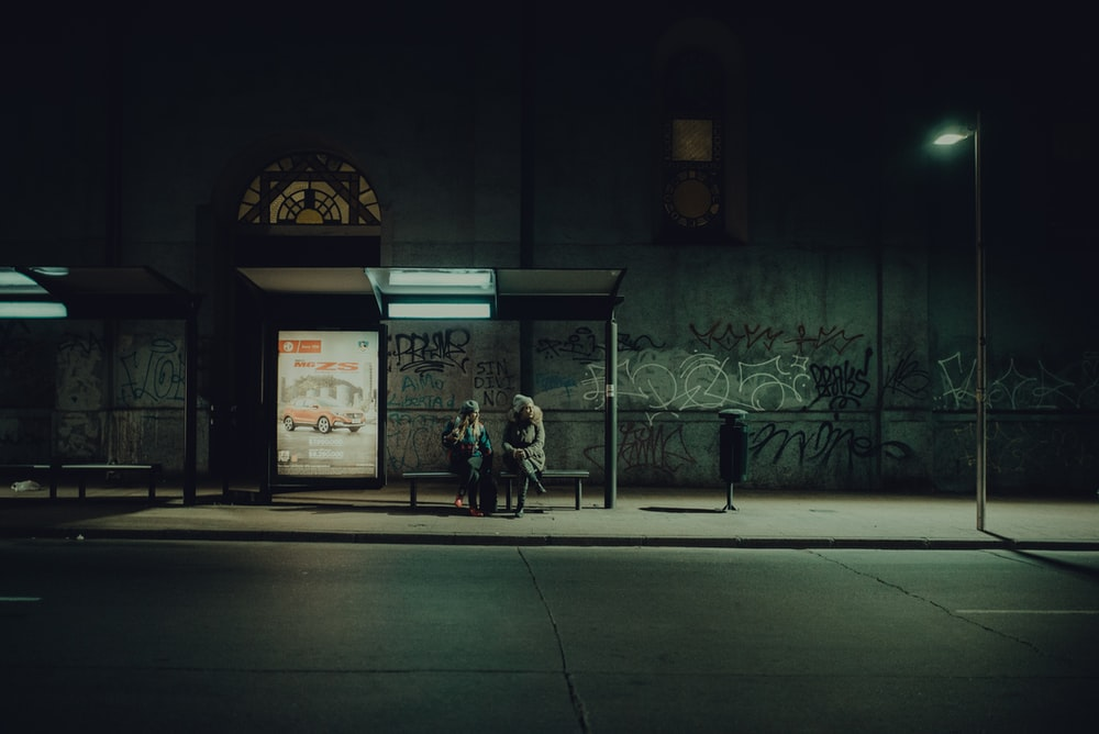 two people sitting on waiting bench