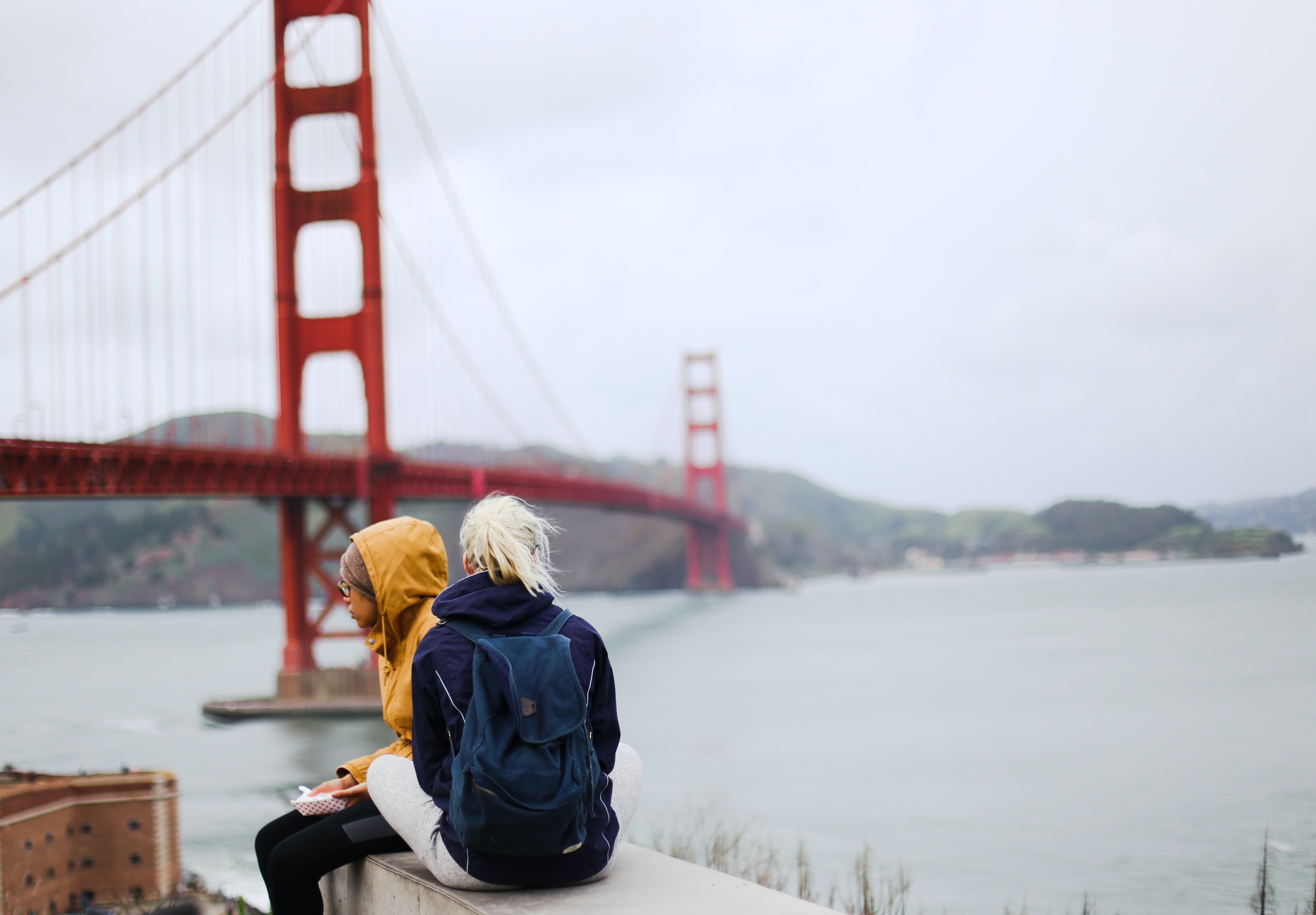 woman sitting on stair near Golden Gate Bridge, San Francisco