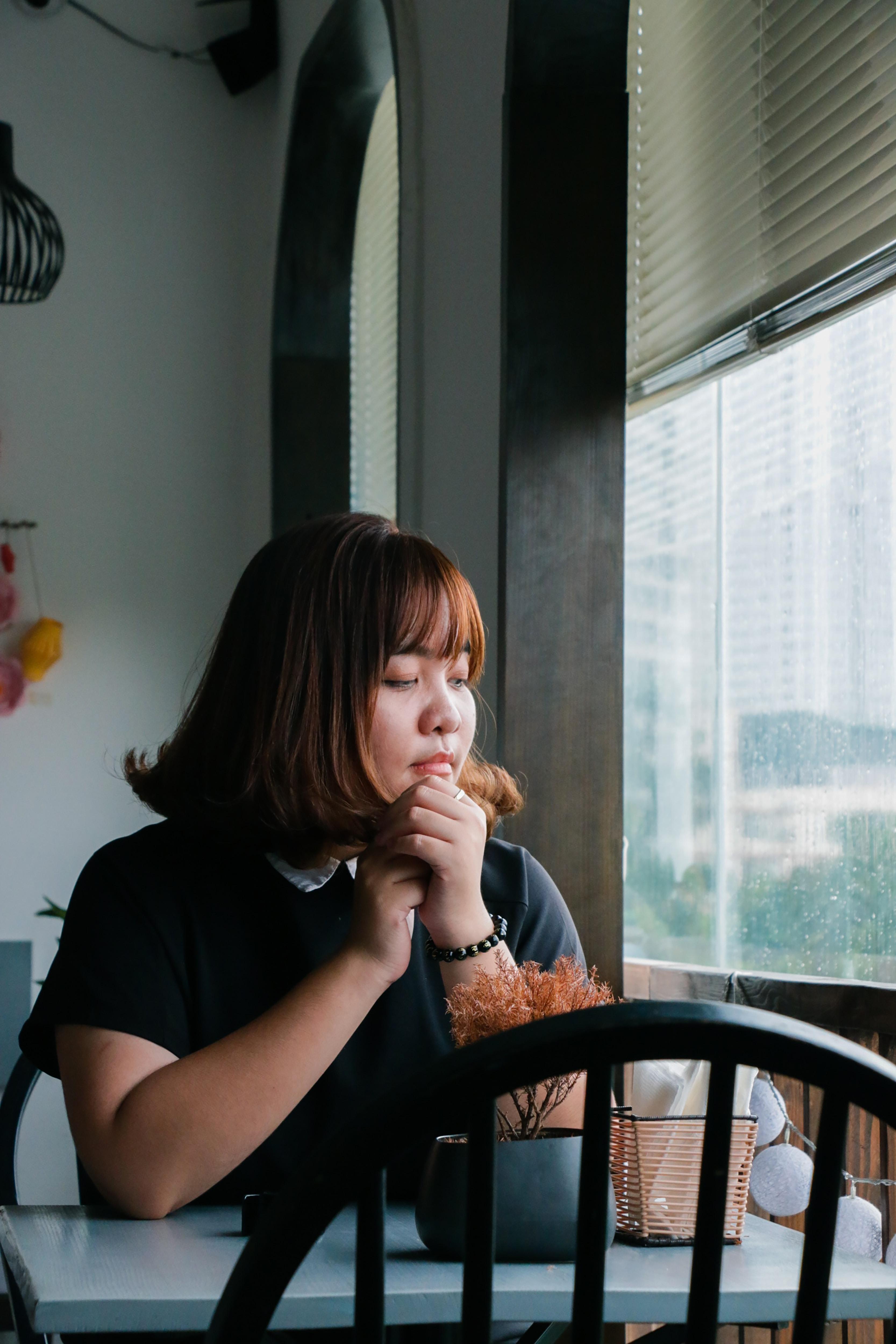 woman sitting near clear glass window