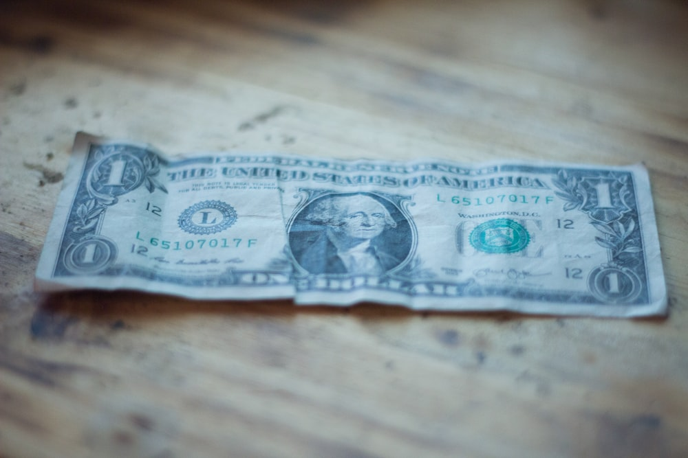 1 US dollar banknote on brown wooden surface