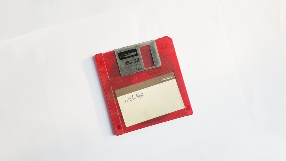 red and white floppy disk on white surface