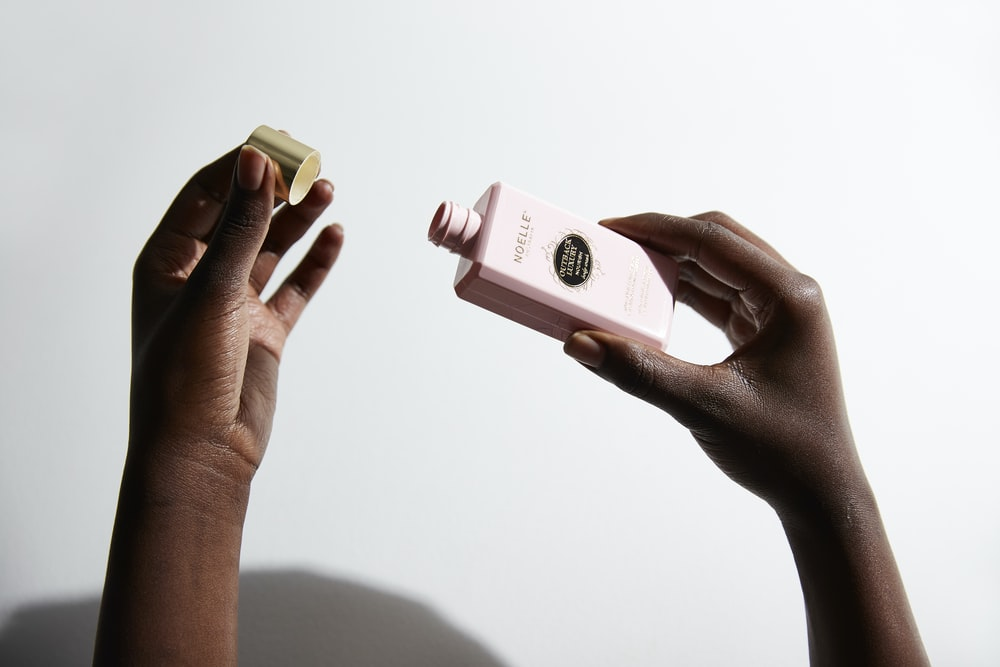 person holding makeup bottle