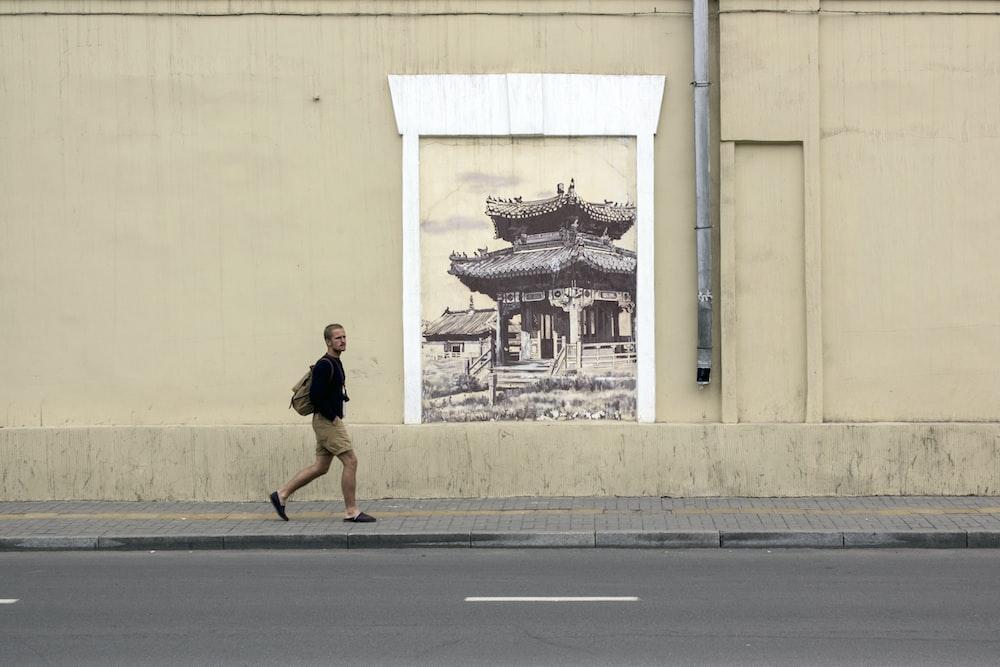 minimalist photography of man walking along pagoda wall artwork