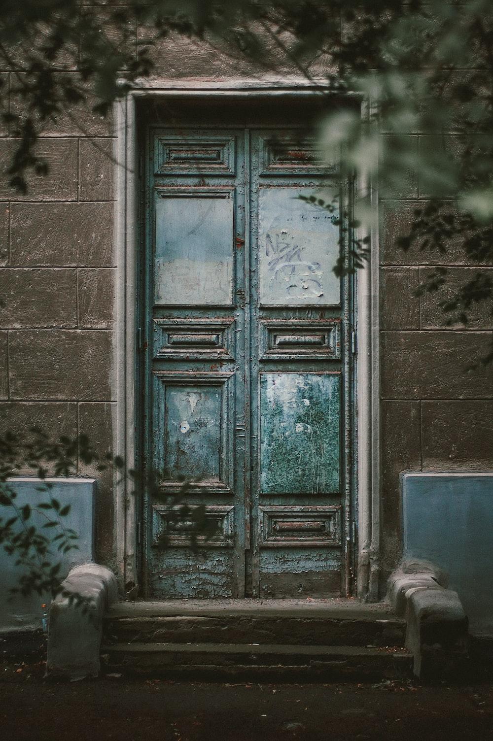 teal wooden door on gray concrete wall