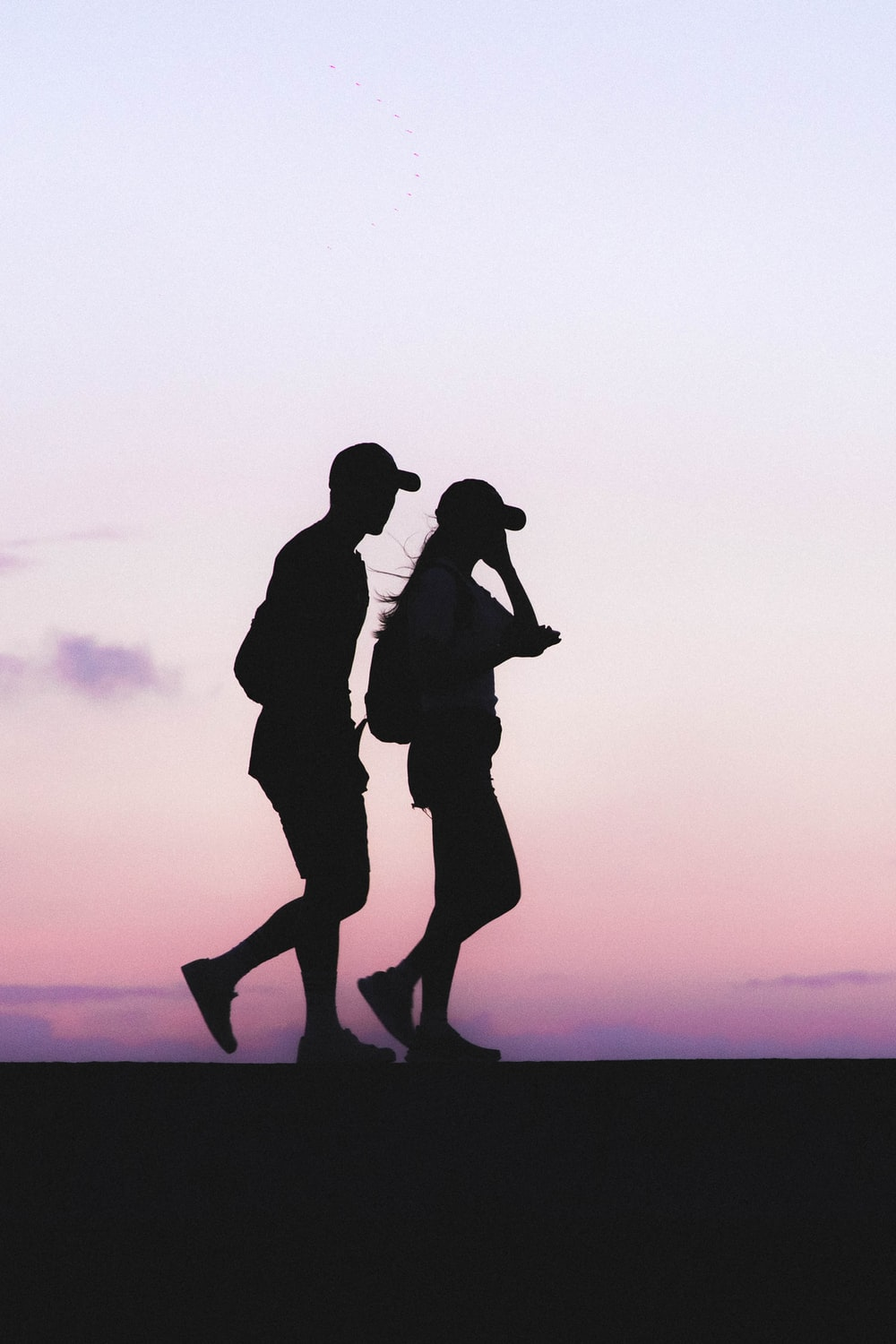 silhouette photo of man and woman wearing caps