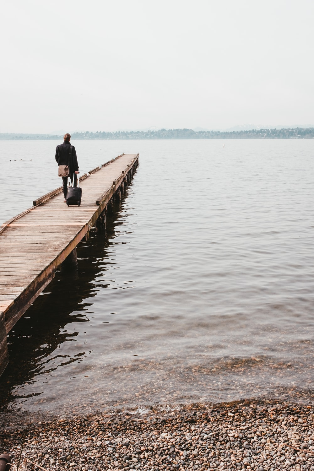 person walking on dock while towing luggage bag