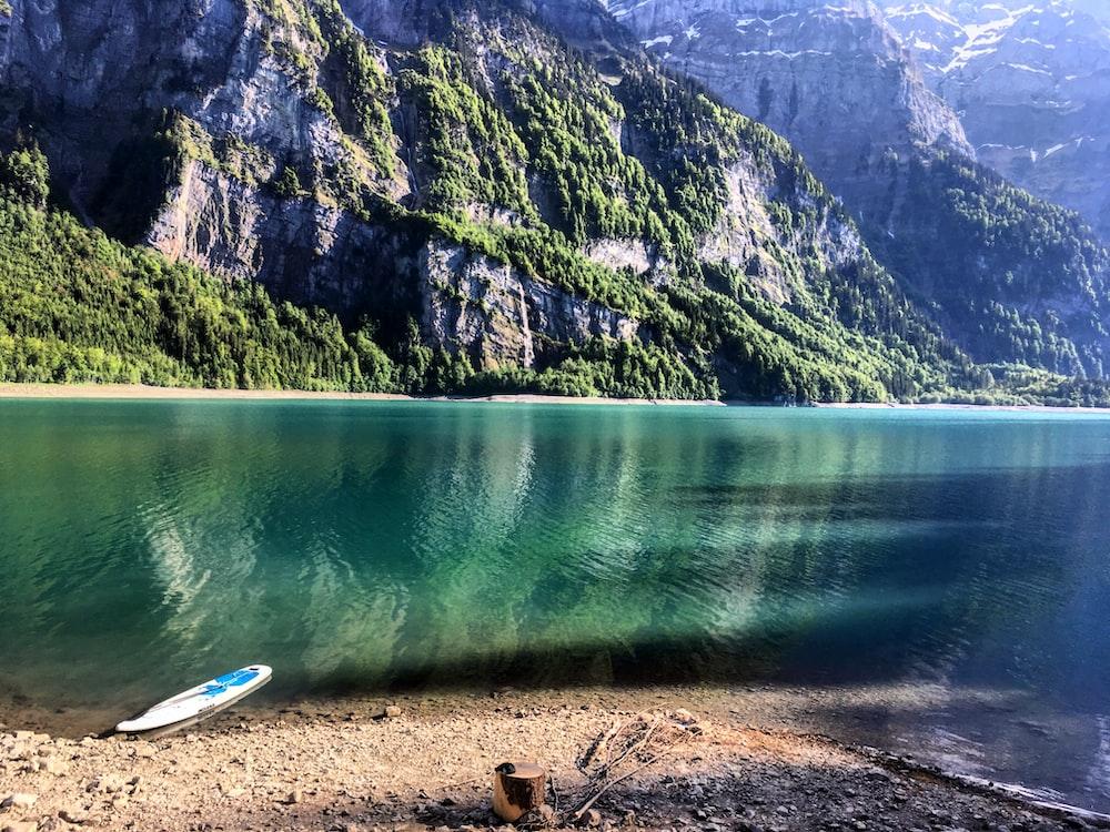 white boat on shore near green mountain