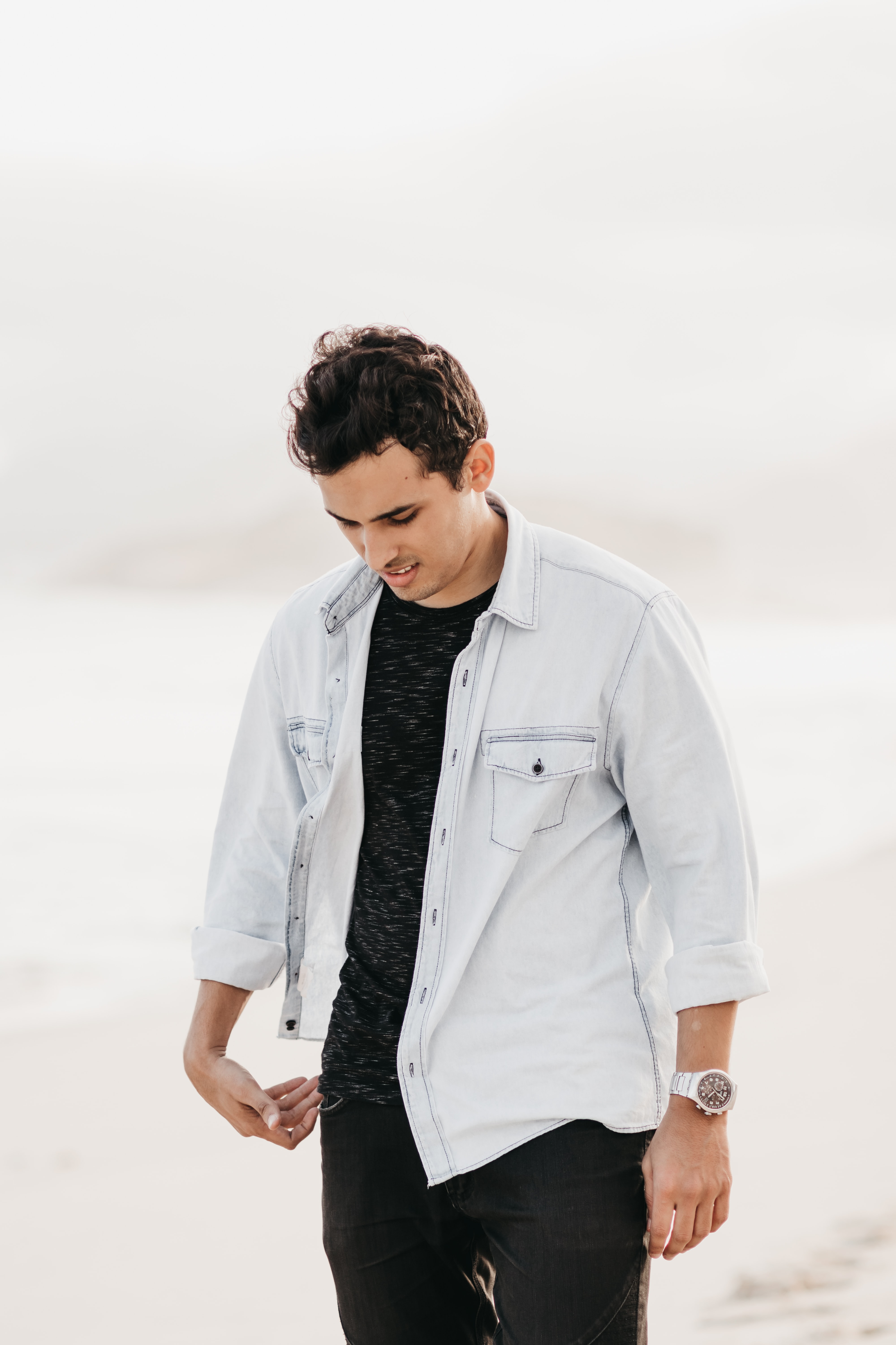 man in white button-up jacket standing in beach