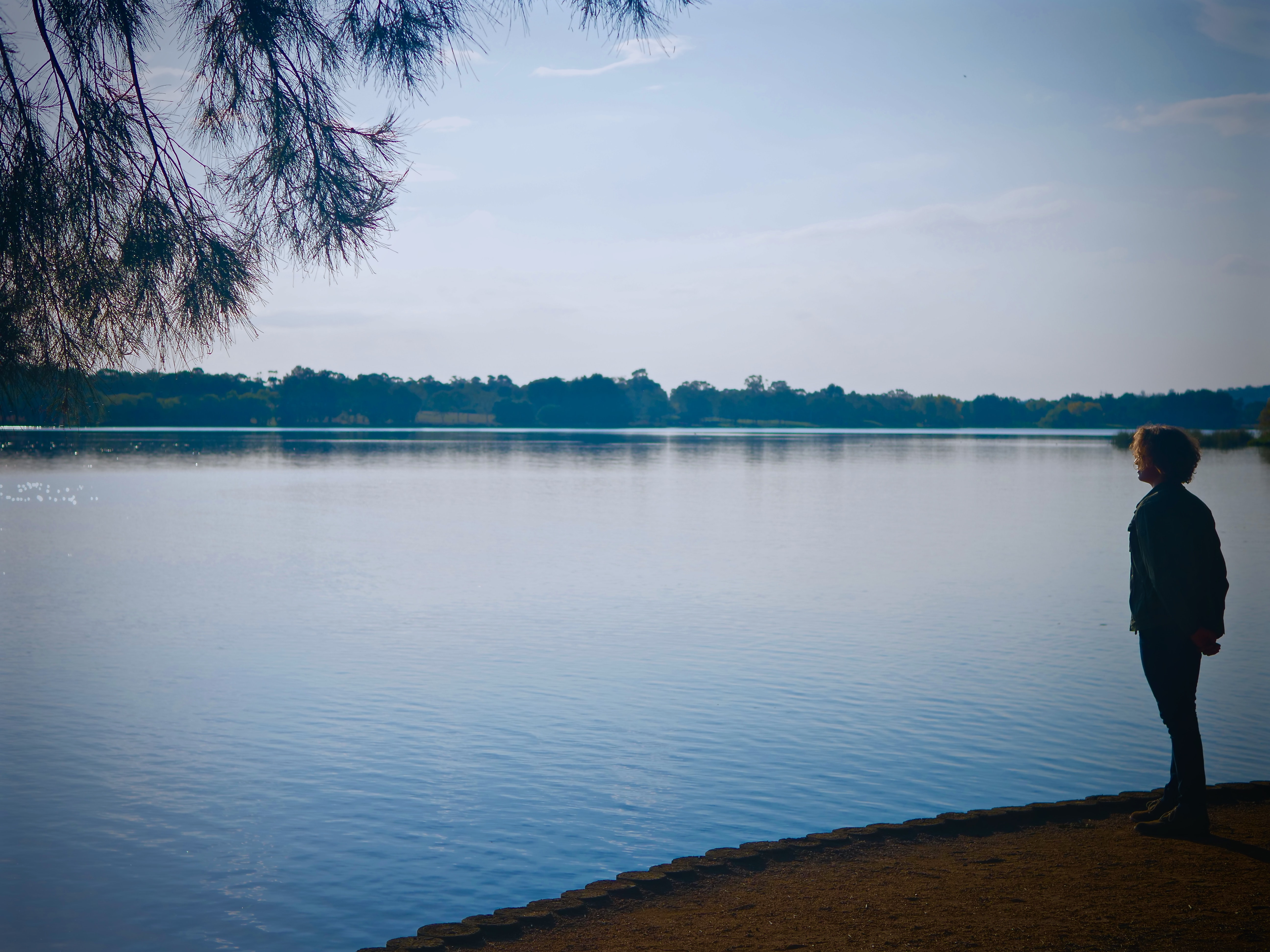 woman standing alone facing body of water