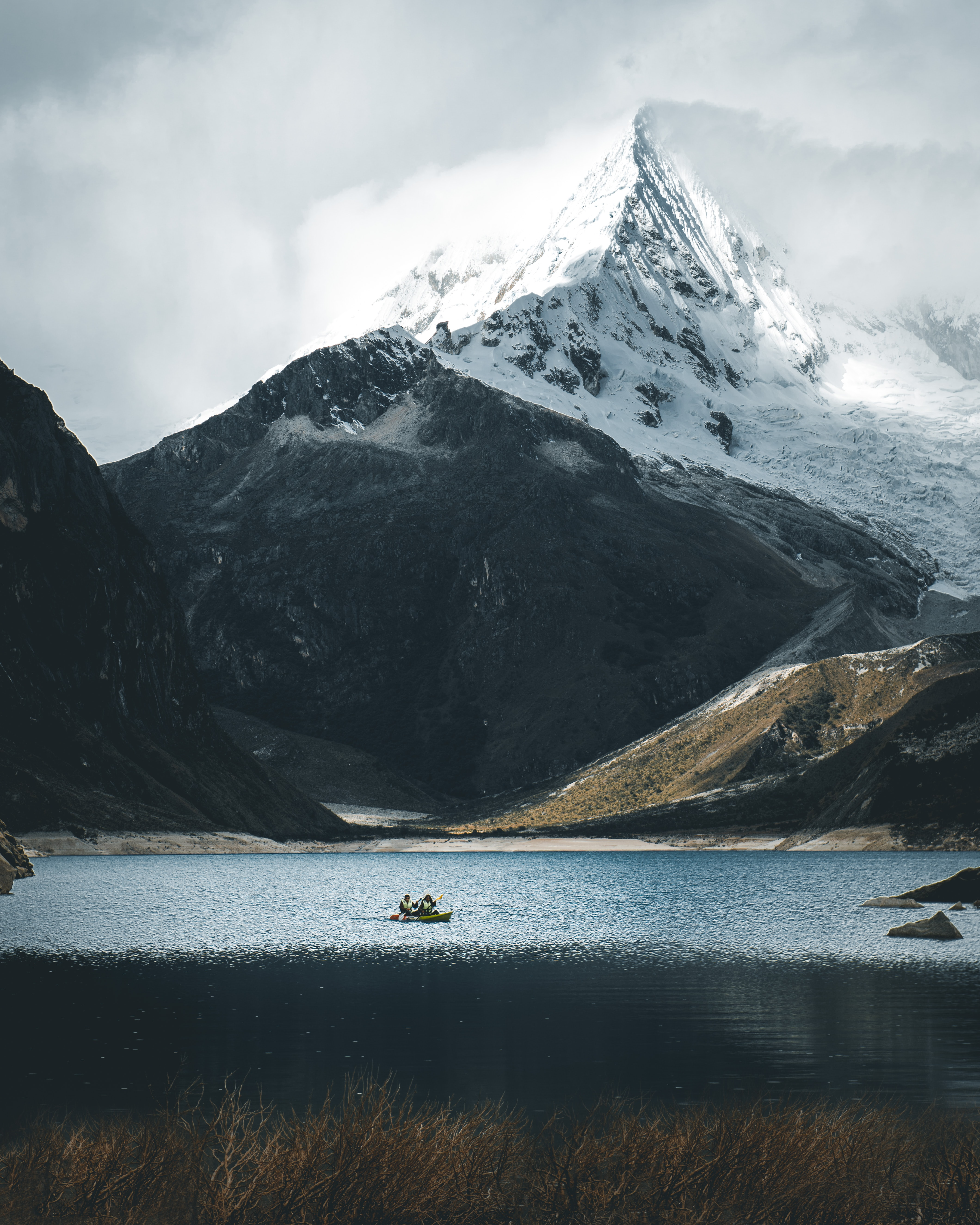 sail boat on body of water beside mountain with snow