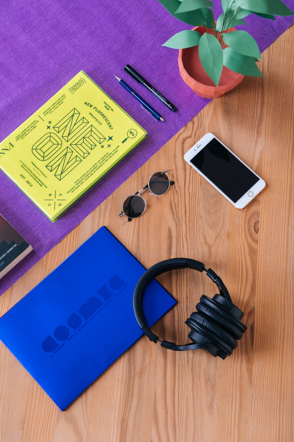 headphones near sunglasses, iPhone 6, and pens on wooden surface