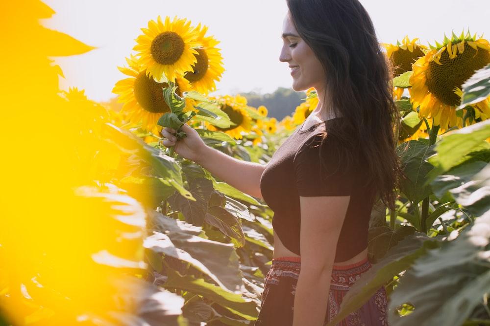 selective focus of woman standing between sunflowers