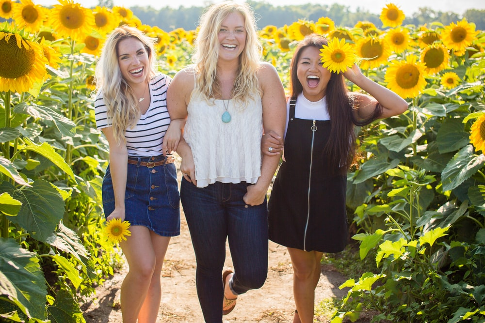 three women standing between sunflowers