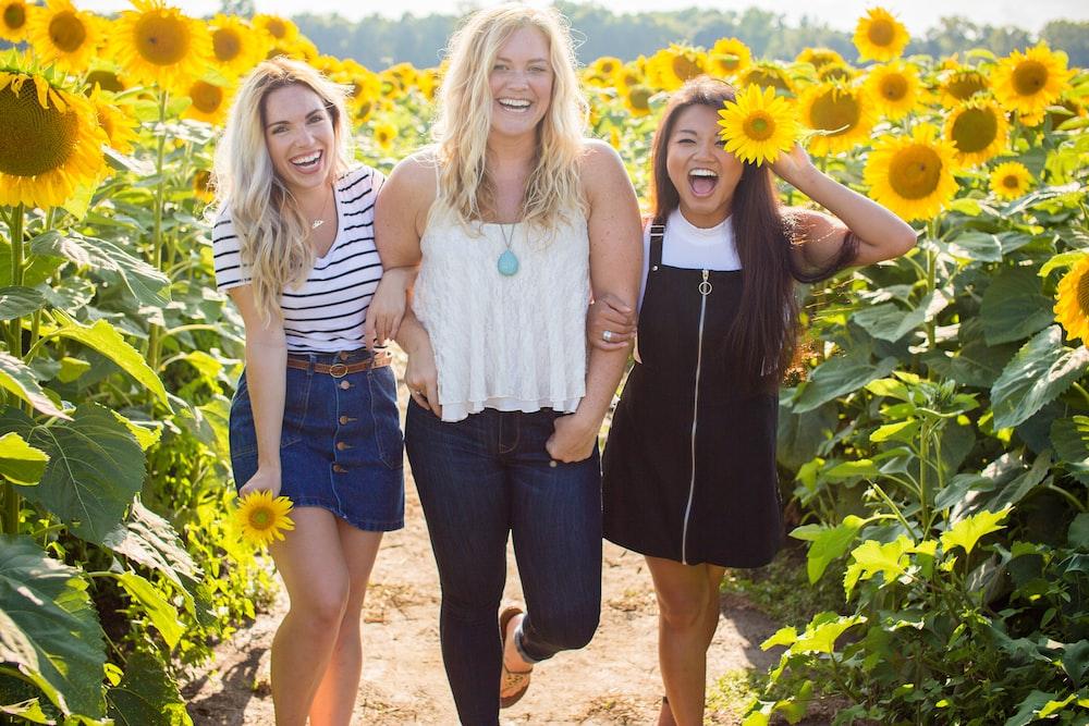three women standing between sunflowers
