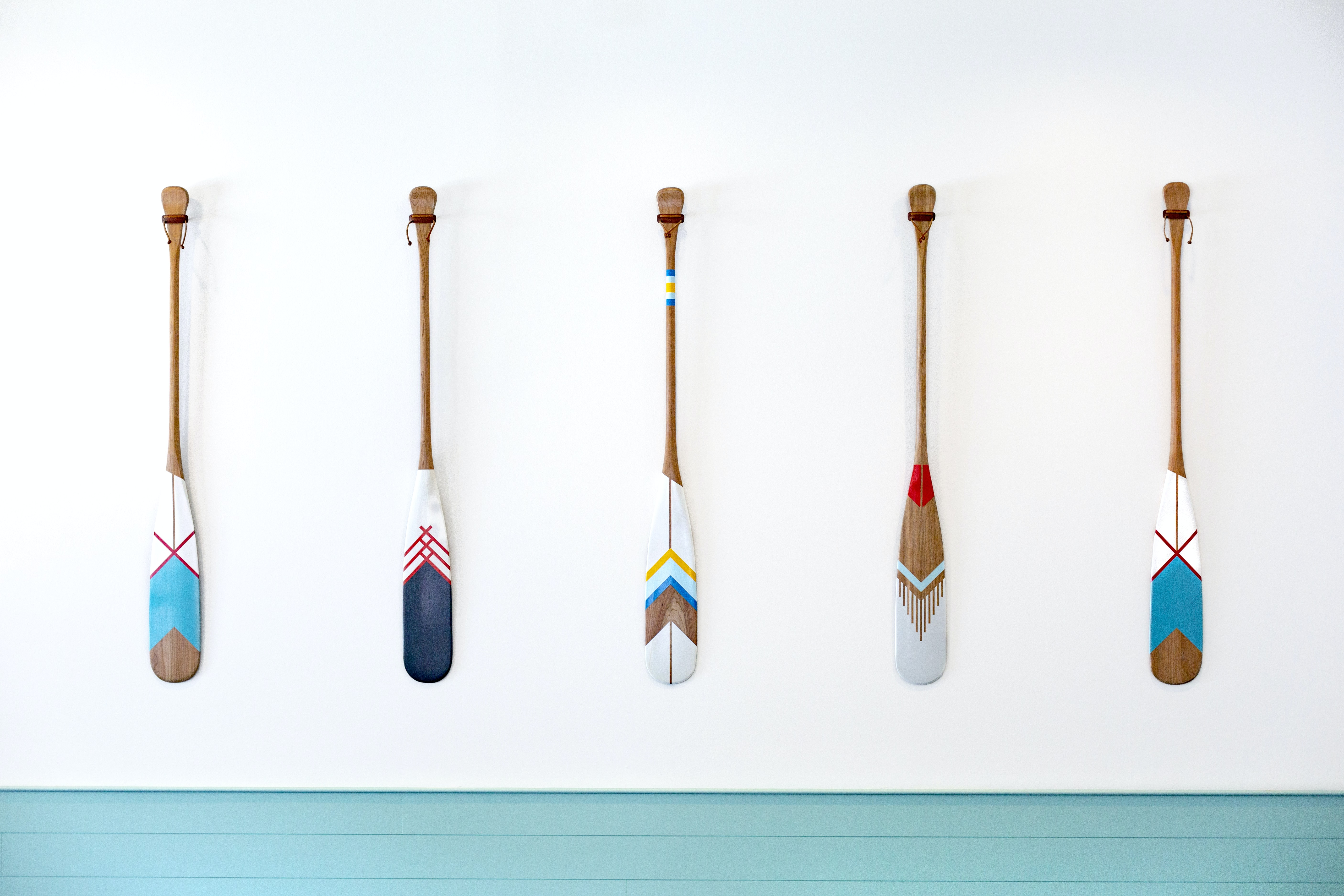 five assorted-color oars on white wall