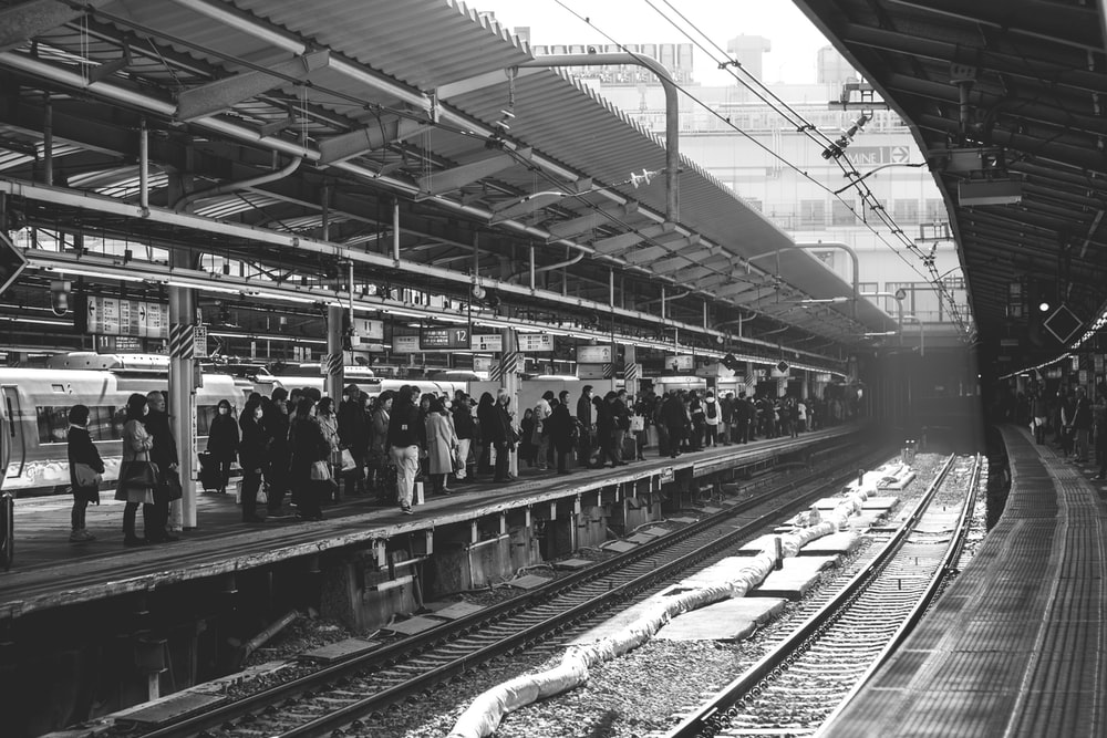 grayscale photo of group of people walking in train station