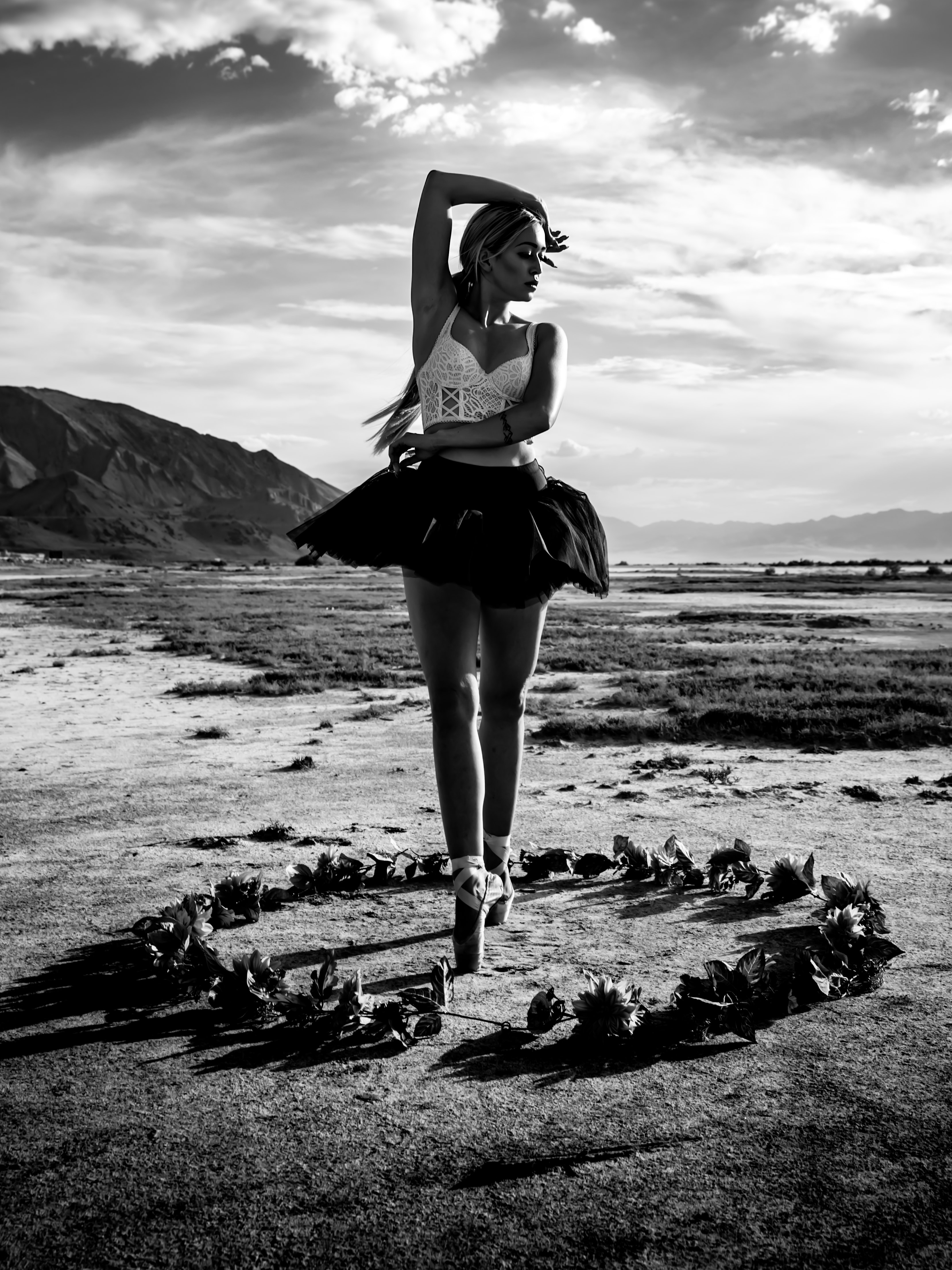 grayscale photography of ballerina tiptoeing in middle of flowers outdoor