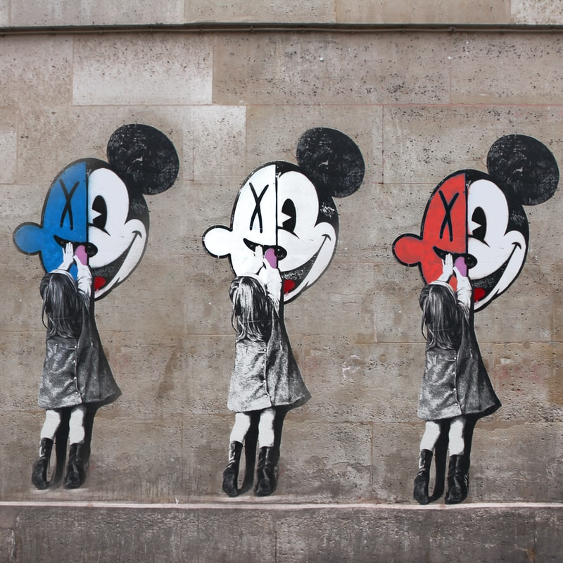 A grey wall with graffiti on it. The graffiti is three mirrored images of a little girl (black and white) reaching up to a picture of a face that is half Mickey Mouse and half a smile with an X over the eyes. The smiling halves are different colours: blue, white, and red.