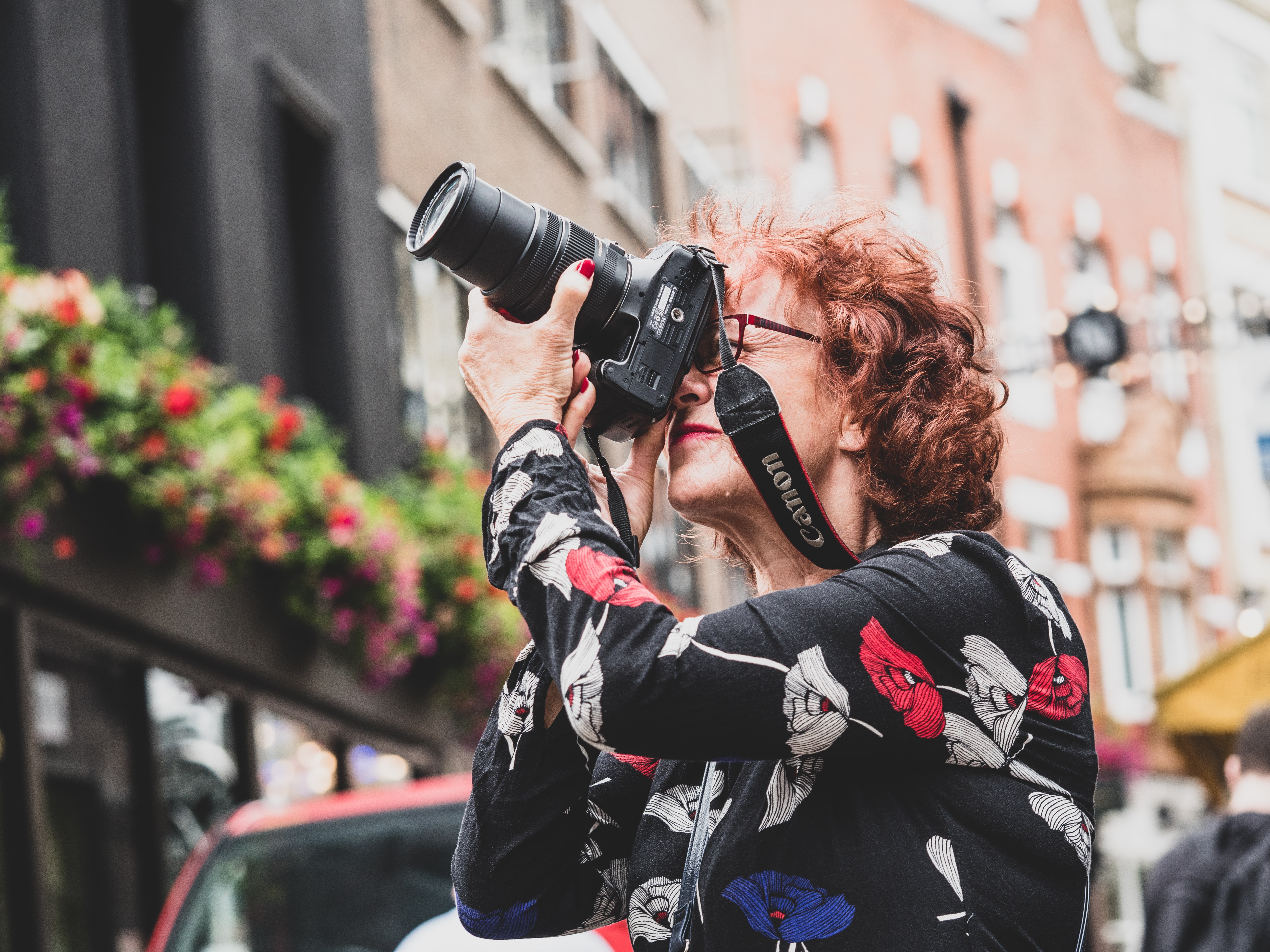 low angle photography of woman holding Canon DSLR camera looking upward