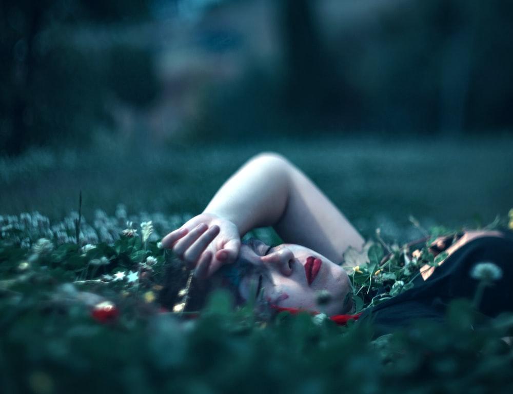 woman closing eyes lying on green grass