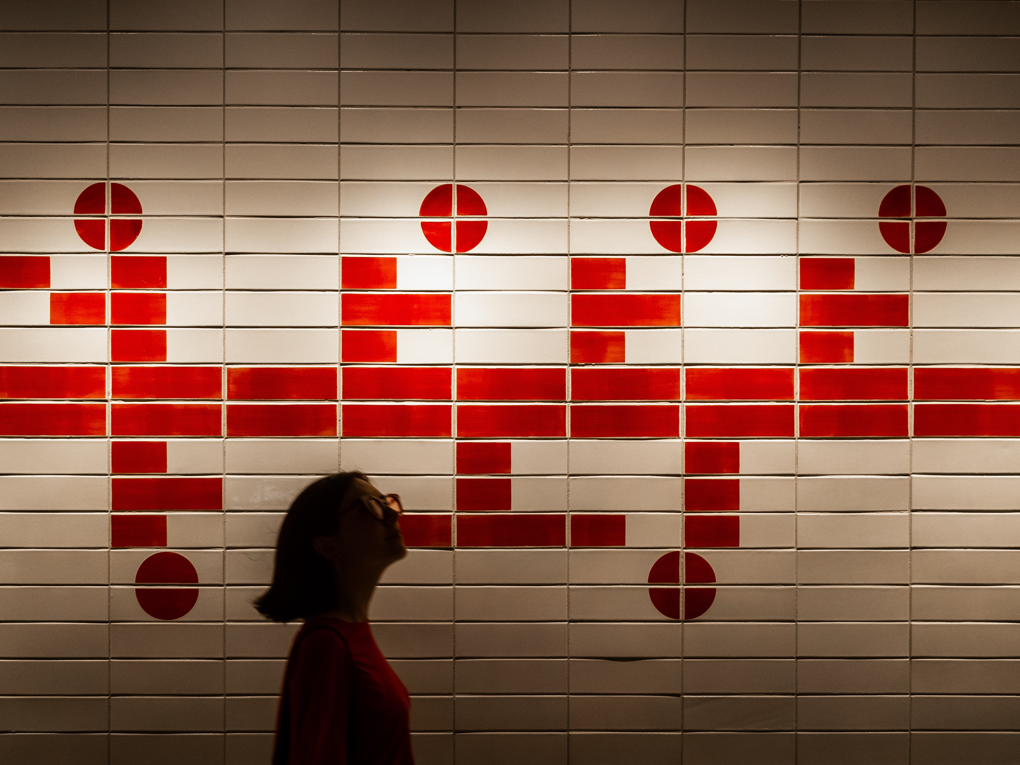 woman standing beside red and white wall