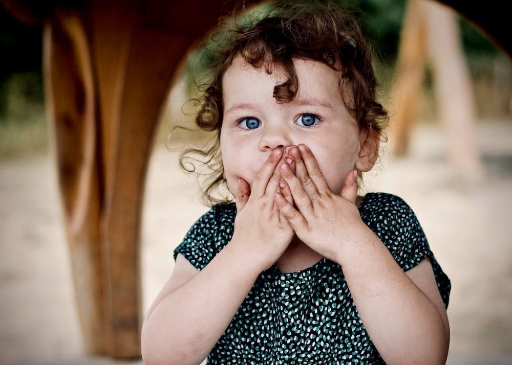 toddler holding her lips