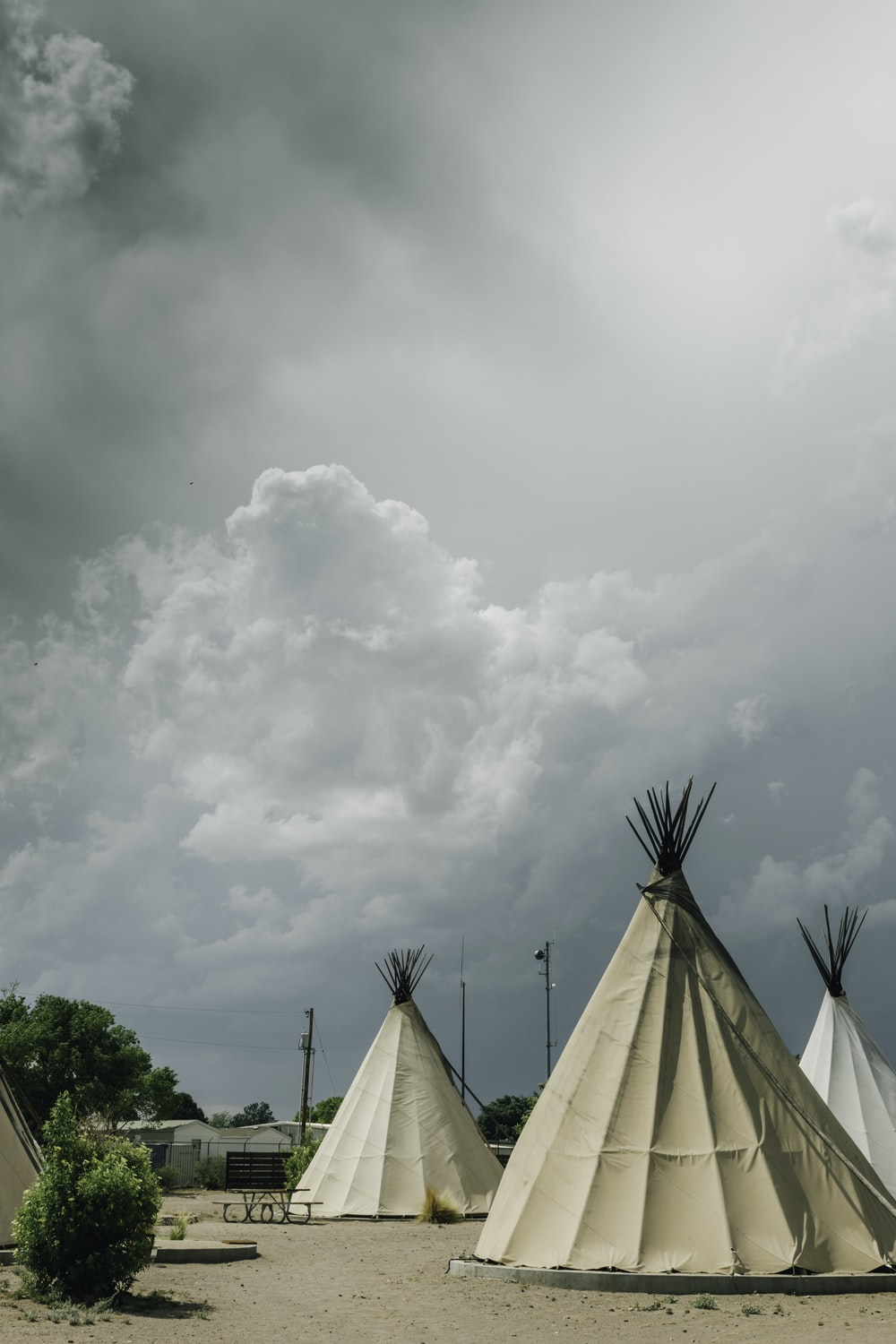 white teepee tents under cloudy sky