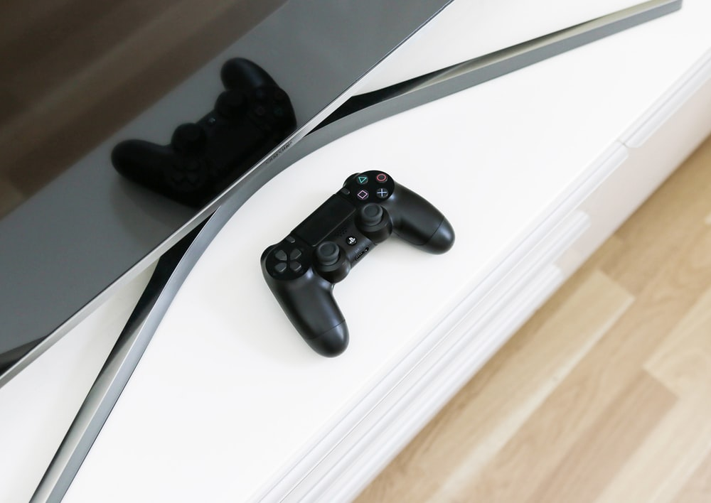 black Sony PS3 controller on white surface