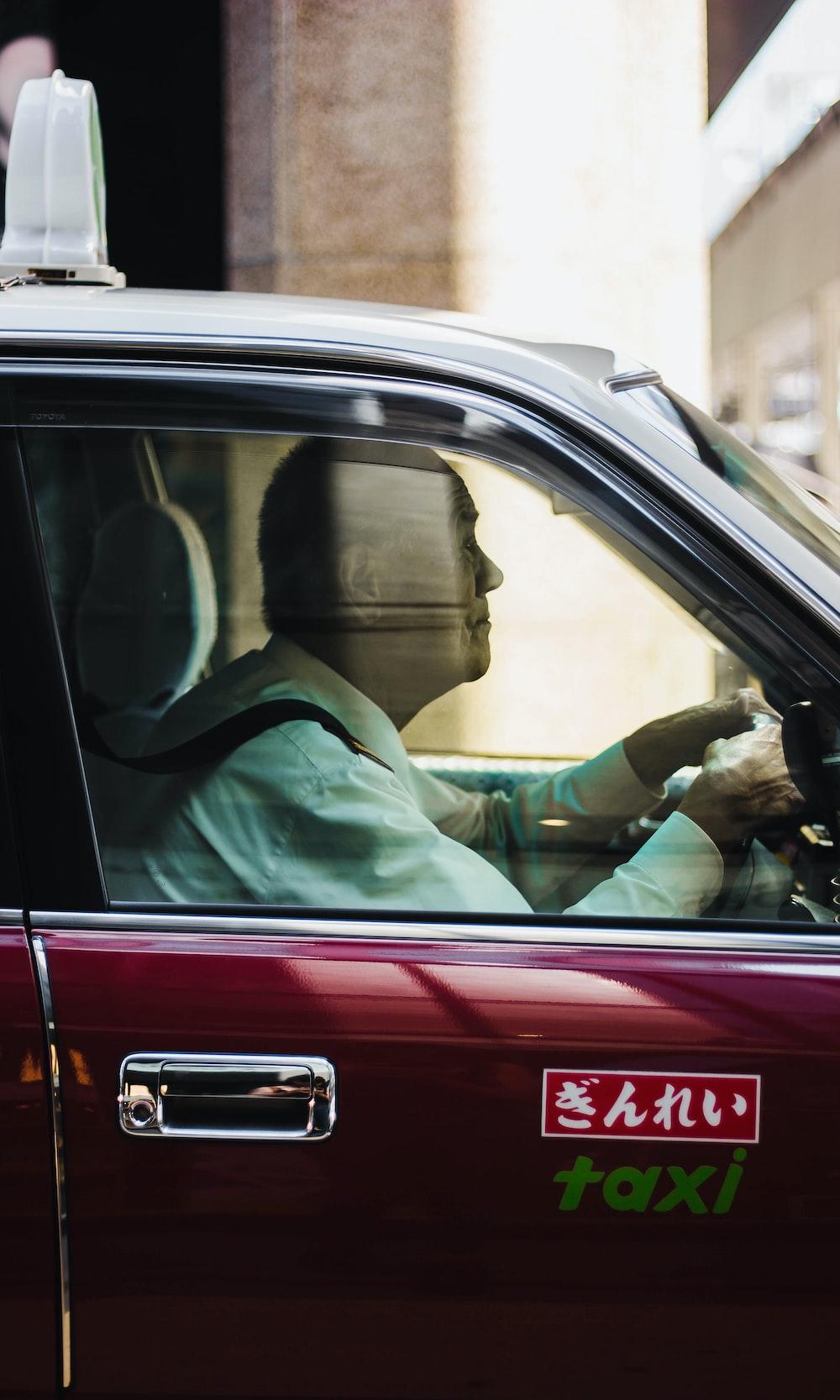 man in green dress shirt driving car during daytime