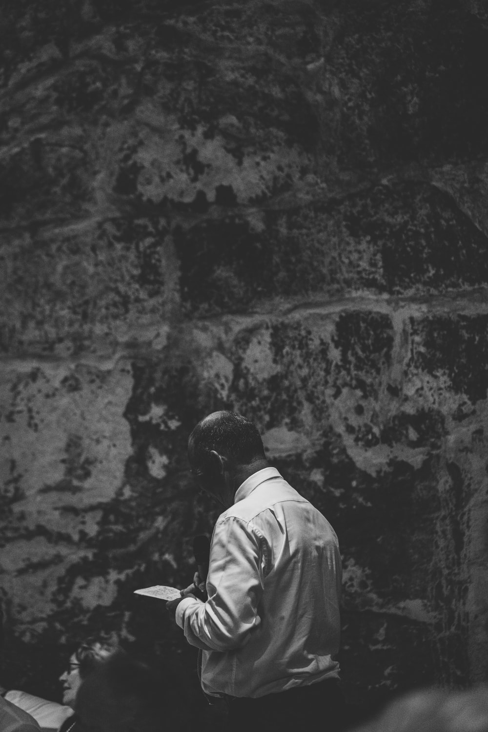 grayscale photography of man walking beside wall