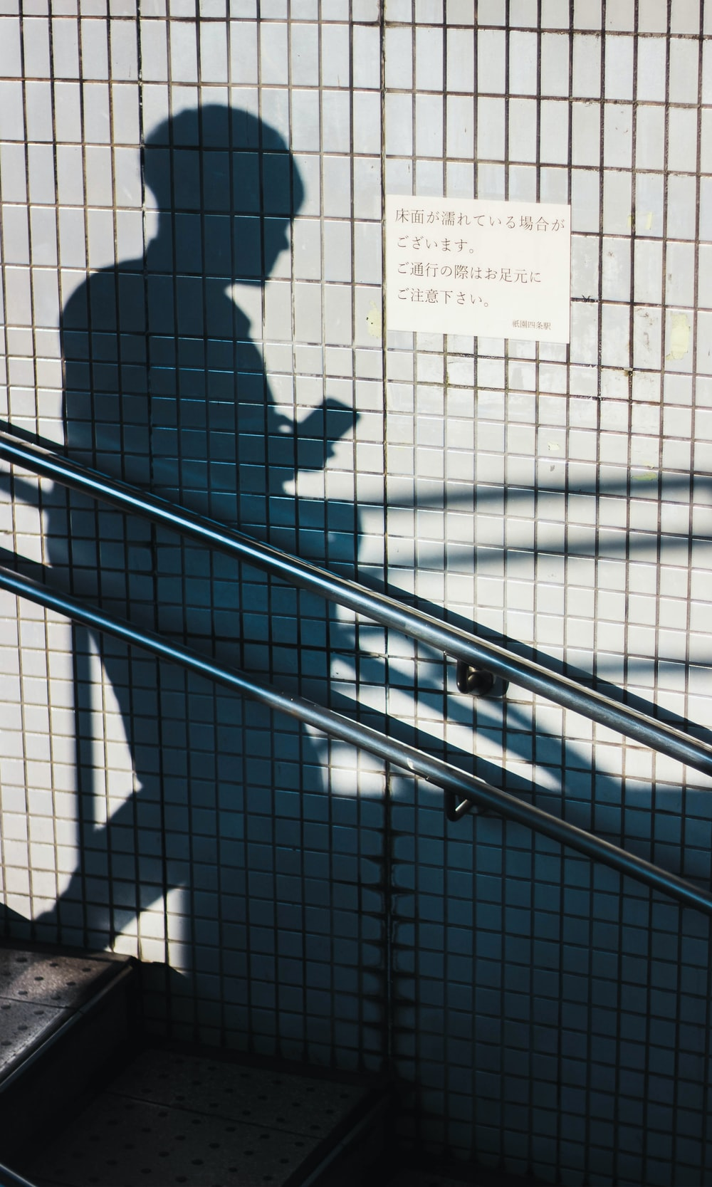 human shadow beside gray wall