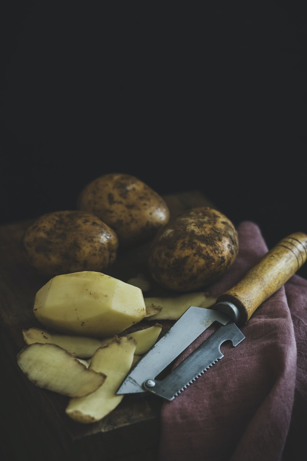 peeled and unpeeled potatoes on top of wooden table