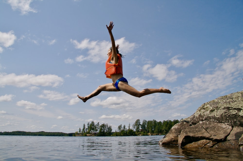 woman jumping towards water wearing life vest