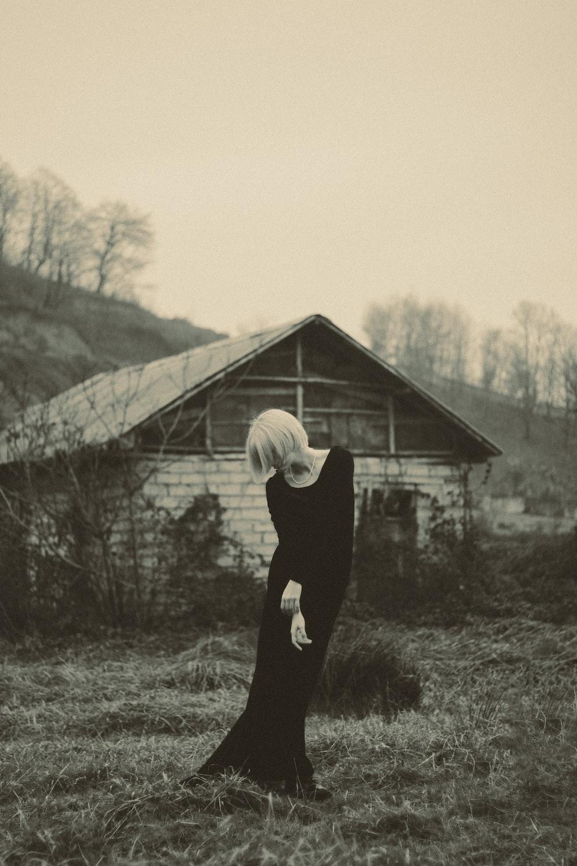 woman in black long-sleeved long dress standing near cabin