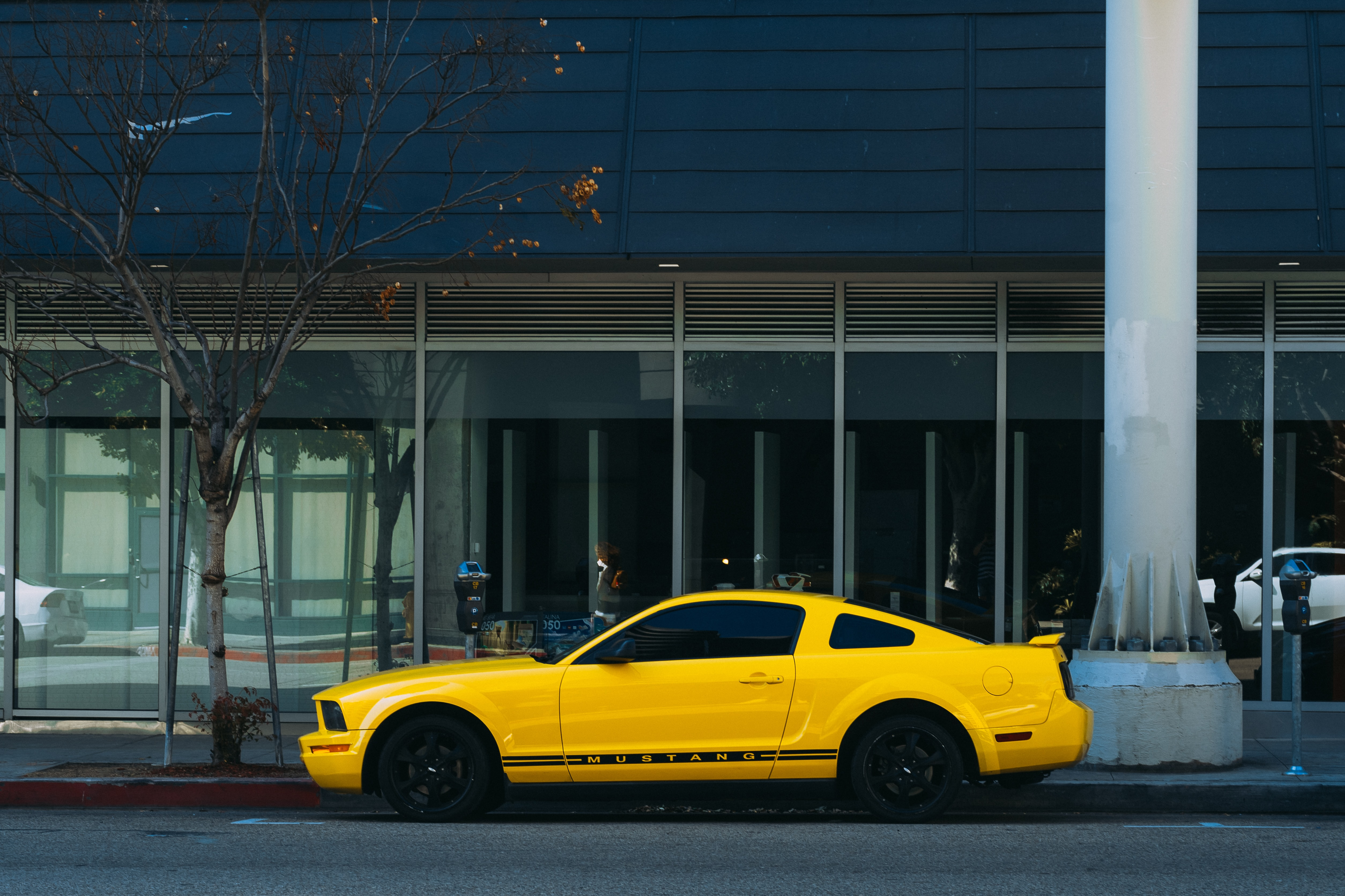 yellow coupe parked outside building