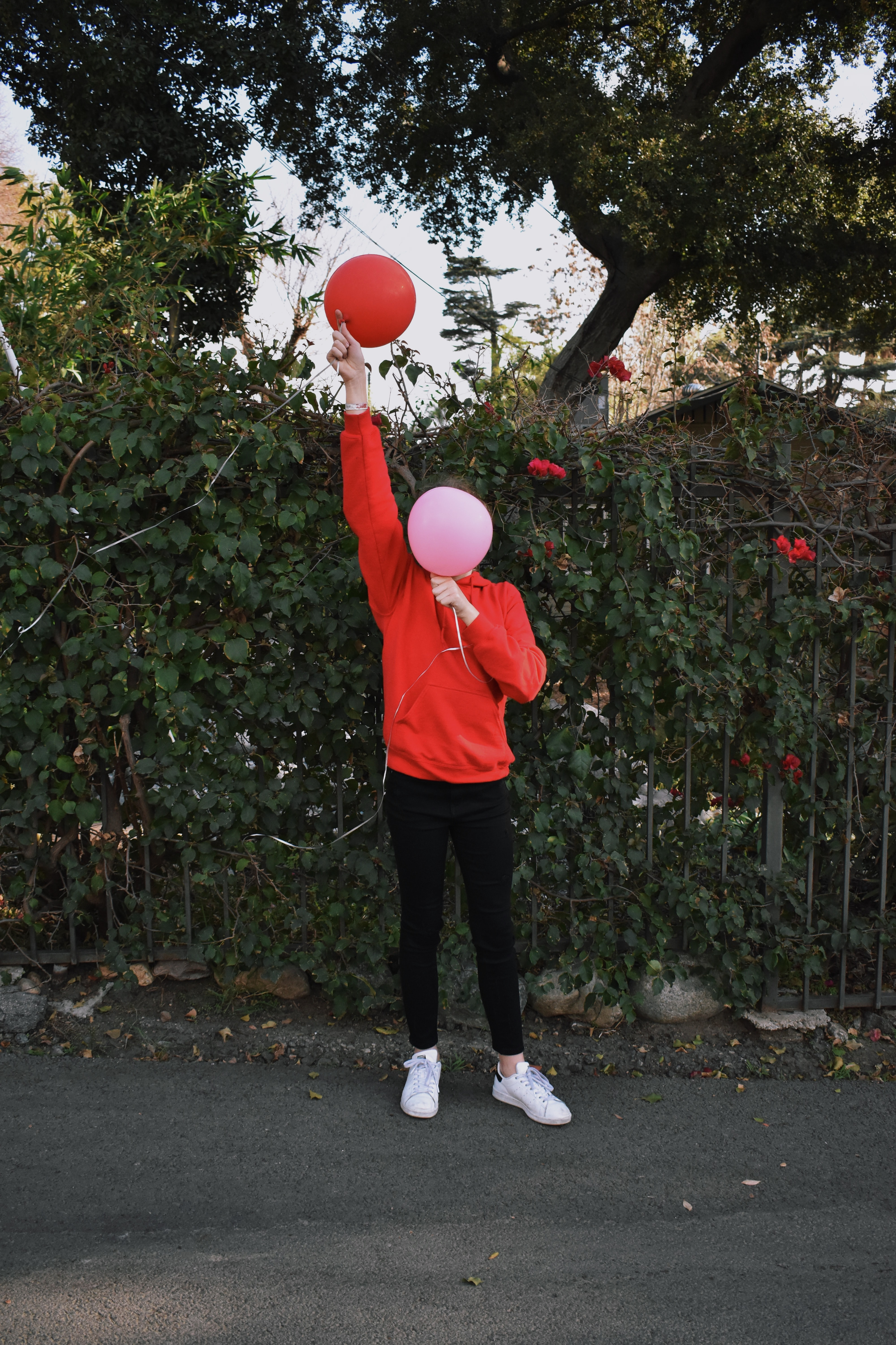 person holding pink and red balloon outdoors