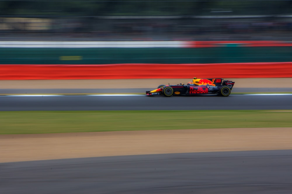 panning photography of race car passing race track
