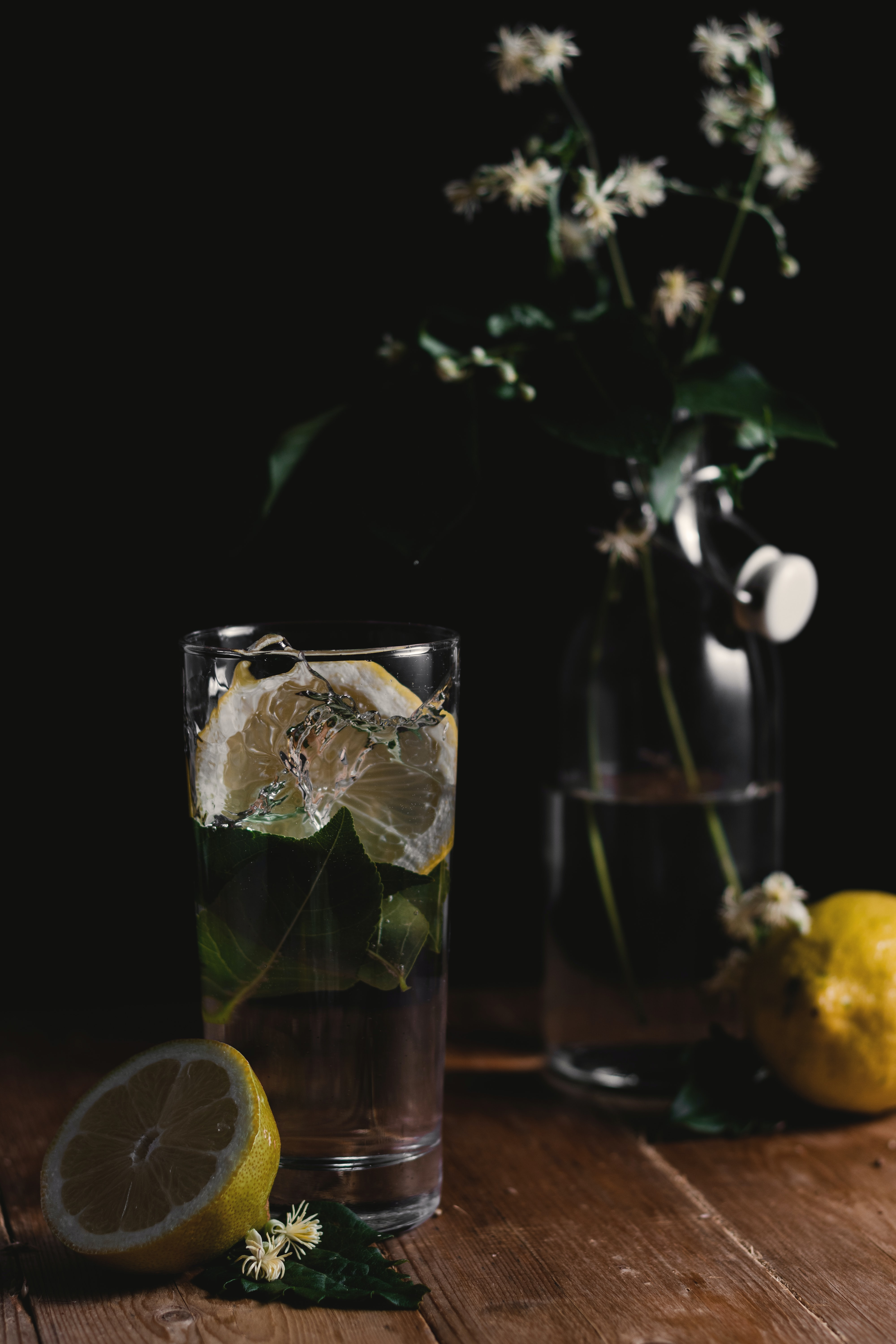 clear drinking glass and sliced lemons on wooden surface