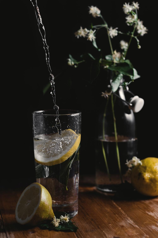clear drinking glass beside flower vase