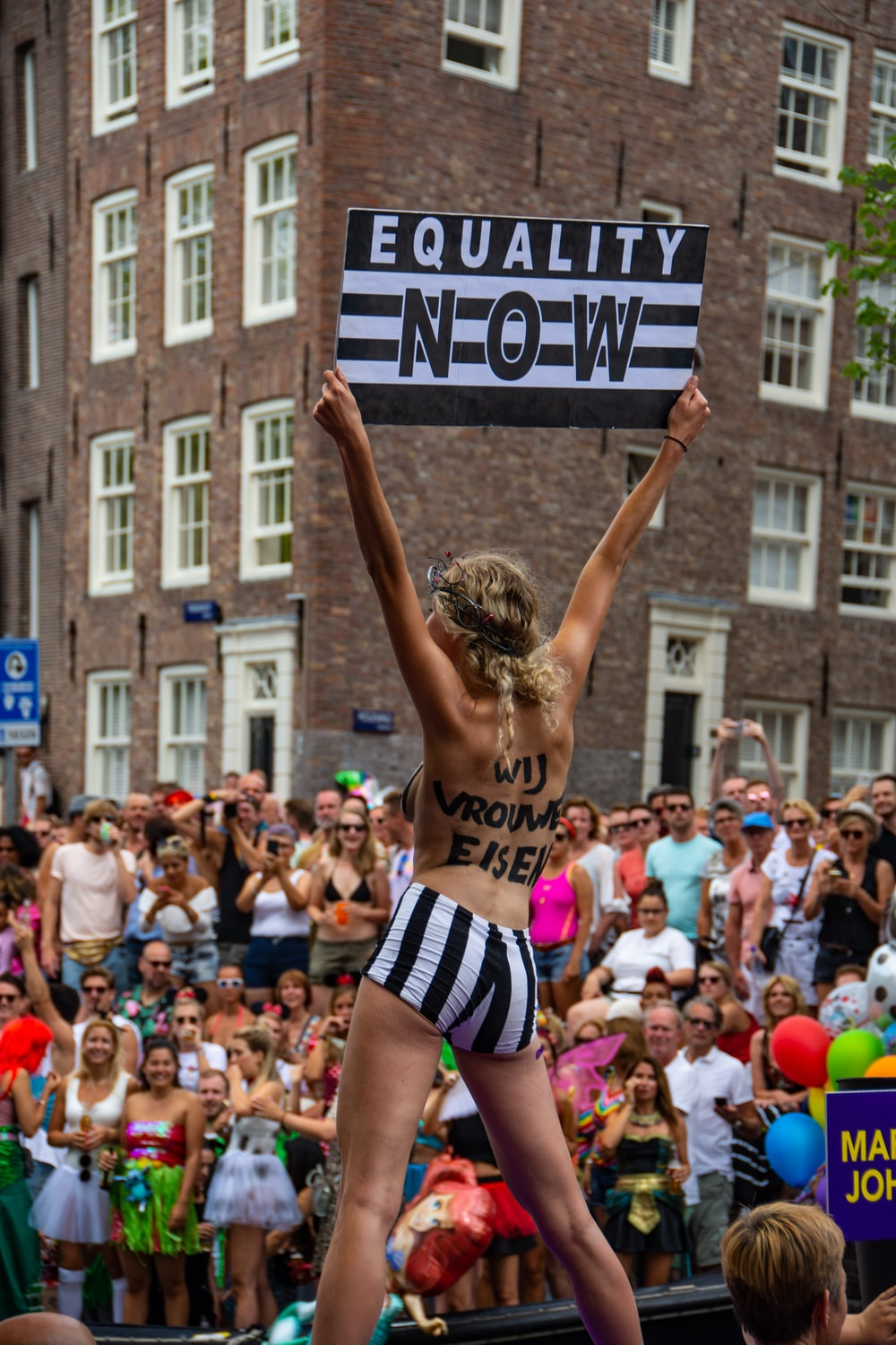 woman holding equality now banner