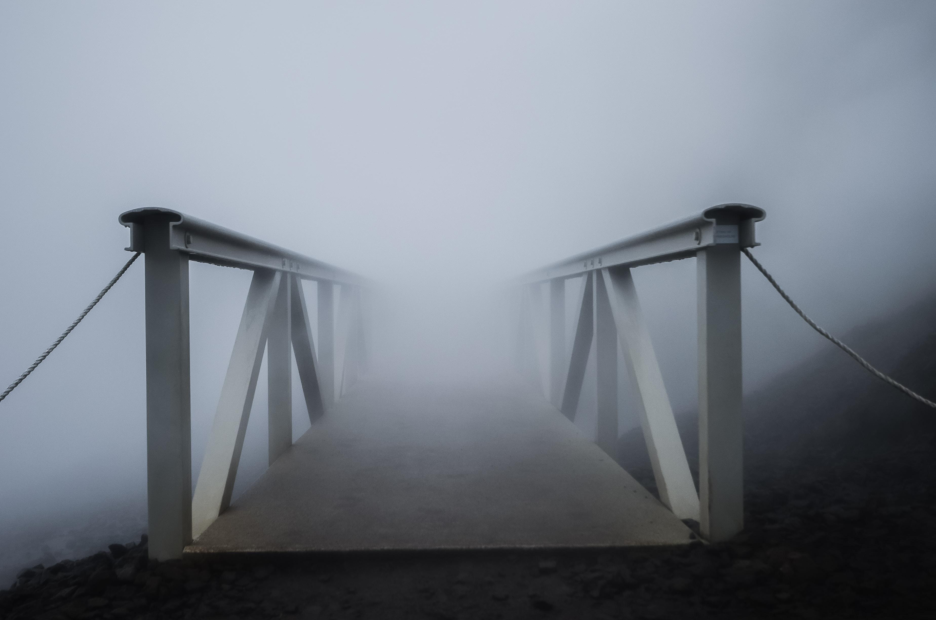 white metal bridge covered in fog
