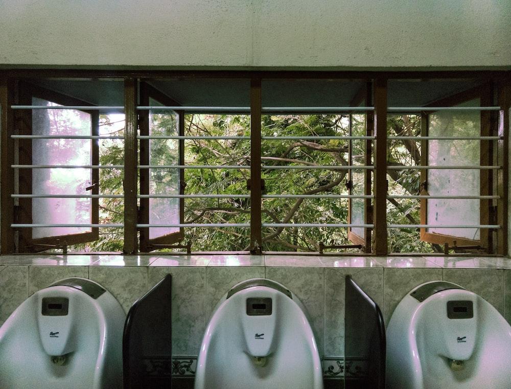 three male urinal in room - Mens Bathroom