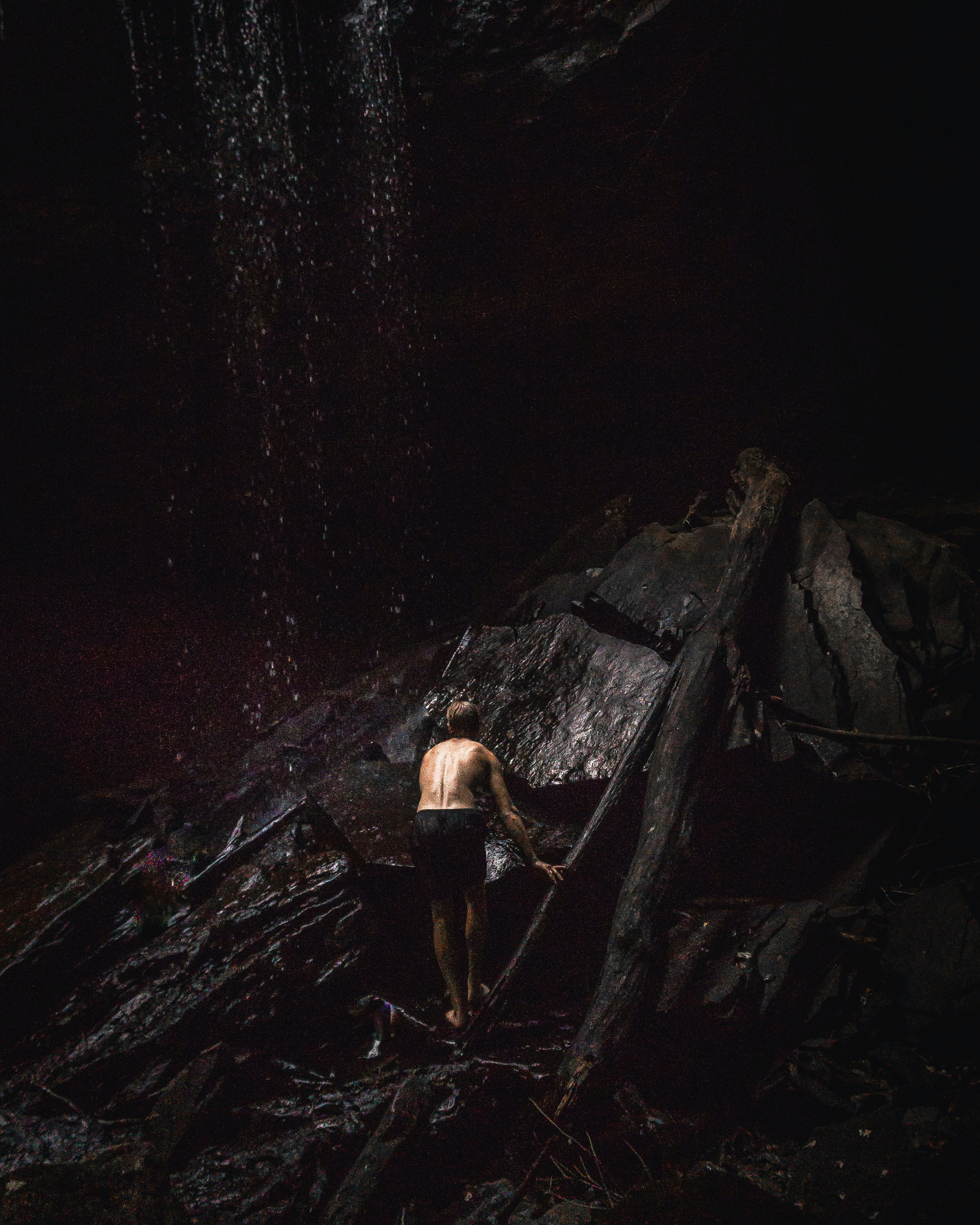 topless man standing at the bottom of waterfall